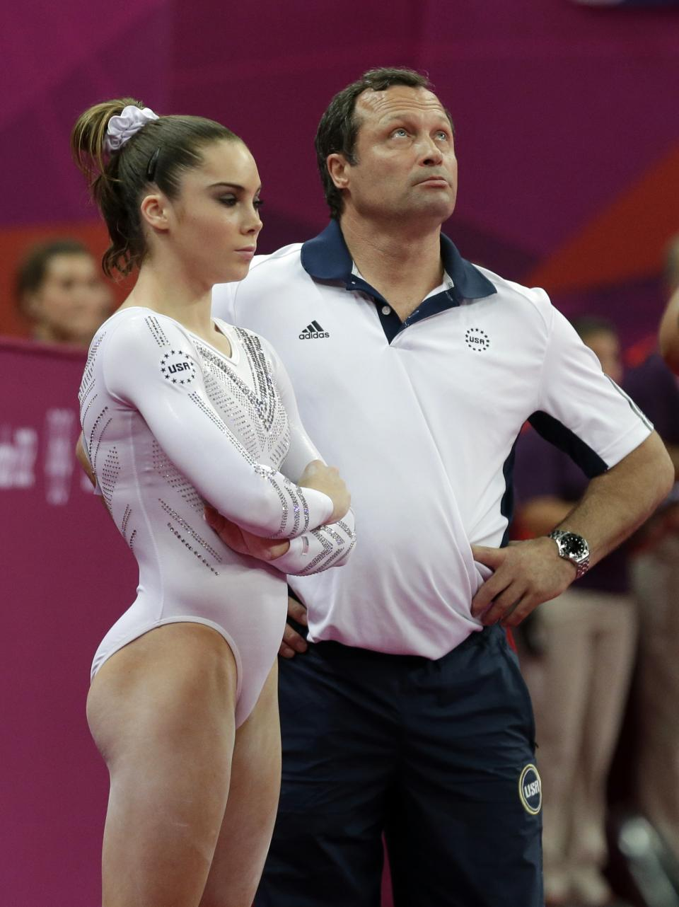 U.S. gymnast McKayla Maroney and her coach wait for the final scores after Romania's gymnast Sandra Raluca Izbasa's performance during the artistic gymnastics women's vault finals at the 2012 Summer Olympics, Sunday, Aug. 5, 2012, in London. (AP Photo/Julie Jacobson)