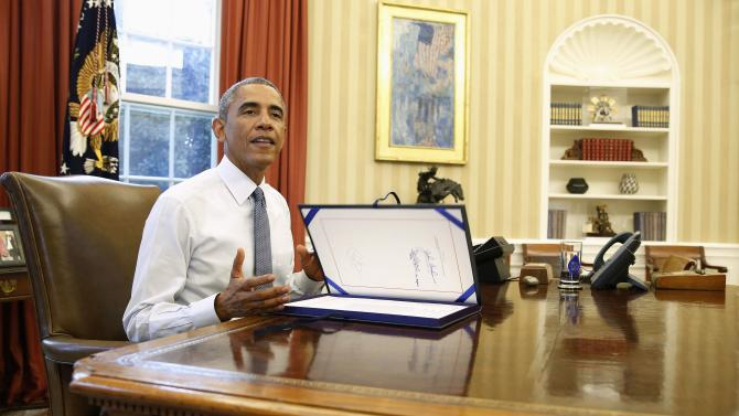 U.S. President Barack Obama looks on after signing H.J. Res. 124, making continuing appropriations for fiscal year 2015, while in the Oval Office of the White House in Washington