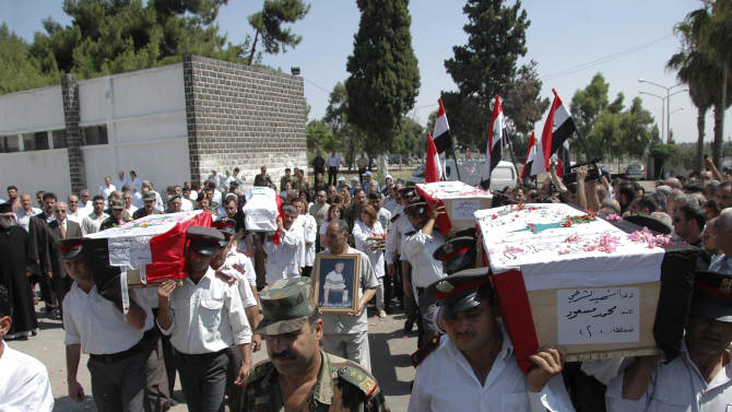 """In this photo released by the Syrian official news agency SANA, Syrian policemen carry the coffins of police and army members who were believed killed in recent violence during their funeral procession outside of a hospital in the central city of Homs, Syria, Monday, July 18, 2011. The discovery of three mutilated corpses set off a wave of sectarian bloodshed that killed up to 30 people over the weekend in central Syria, a dangerous escalation in violence stemming from the country's four-month-old uprising, activists said Monday. The Arabic on the coffin right reads:"""" The martyr policeman Mohammed Massoud."""" (AP Photo/SANA) EDITORIAL USE ONLY"""