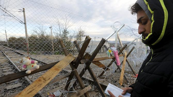 A stranded Iranian migrant prays by a fence at the Greek-Macedonian border.