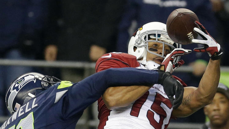 Arizona Cardinals wide receiver Michael Floyd (15) makes a catch for a touchdown around the defense of Seattle Seahawks cornerback Byron Maxwell, left, in the second half of an NFL football game, Sunday, Dec. 22, 2013, in Seattle. (AP Photo/Elaine Thompson)