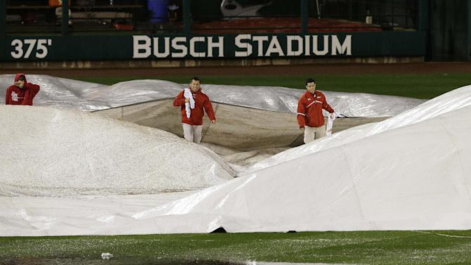 Ground crew prepares the field during the rain delay of Game 3 of baseball's National League championship series between the St. Louis Cardinals and the San Francisco Giants, Wednesday, Oct. 17, 2012, in St. Louis. (AP Photo/Patrick Semansky)