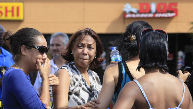 Family and friends gather at the scene of the shooting at Las Dominicanas M&M Salon in Winter Park, Fla., Thursday, Oct. 18, 2012. A gunman opened fire in a central Florida beauty salon Thursday, killing three women and wounding a fourth before killing himself at a nearby home, police said. The shooting appeared to be part of a domestic dispute. (AP Photo/Julie Fletcher)