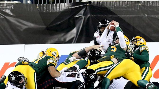 Edmonton Eskimos' Jordan Lynch falls over the top of a group of players to score a touchdown against the Ottawa Redblacks during the CFL's 103rd Grey Cup championship football game in Winnipeg