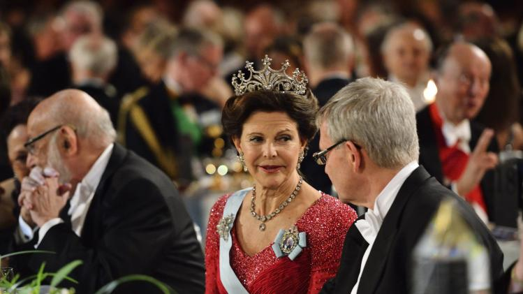 Sweden's Queen Silvia talks to Carl-Henrik Heldin, head of the Nobel foundation board, during the Nobel gala banquet in Stockholm