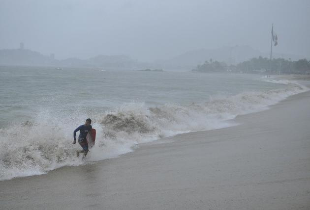 A surfer runs off a beach during rainfall brought on by Hurricane Raymond in Acapulco