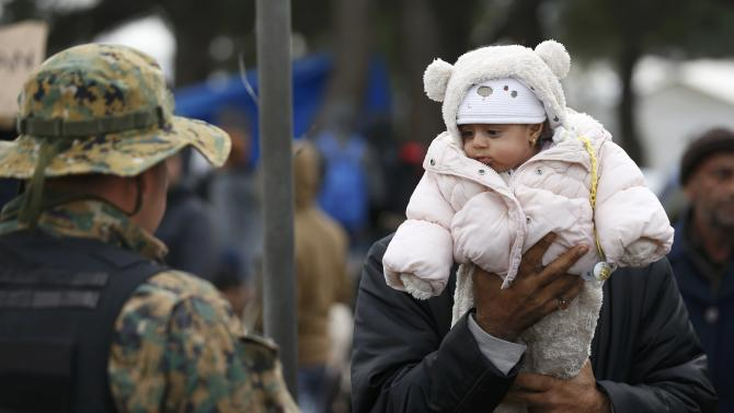A migrant holds a child in front of police as he waits to cross the border from Greece into Macedonia, near Gevgelija