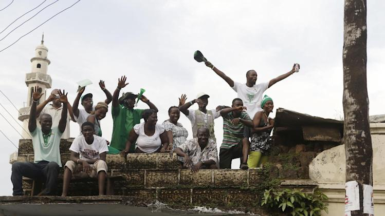 Supporters of opposition candidate Julius Maada Bio wave from a rooftop as Bio's campaign convoy passes en route to his final rally in Freetown, Sierra Leone Thursday, Nov. 15, 2012. Ten years after the end of a devastating civil war, Sierra Leone will go to the polls on Saturday to choose between candidates including Bio and incumbent President Ernest Bai Koroma. (AP Photo/Rebecca Blackwell)