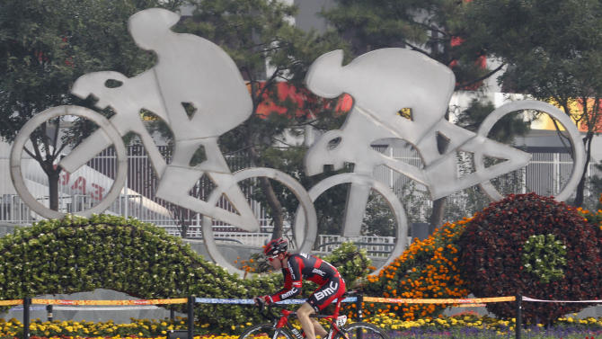 Yannick Eijssen from team BMC rides past the sculptures of cyclists before the start of time trials of the UCI Tour of Beijing cycling competitions held in Beijing, China, Wednesday, Oct. 5, 2011. (AP Photo/Ng Han Guan)
