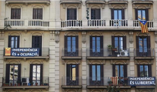 Catalan separatist flags and banners hang from balconies in a building at Barcelona