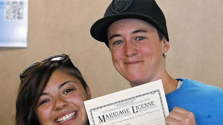 FILE - In this July 10, 2014 file photo, Samantha Getman, right, and Victoria Quintana show their marriage license at the Denver Clerk's office. Colorado's Supreme Court has ordered an end to gay marriages while the state's ban against the unions remains in place. The state's high court on Friday, July 18, 2014, ordered Denver's clerk Debra Johnson to stop issuing marriage licenses to same-sex couples pending a ruling on the constitutionality of the gay marriage ban. (AP Photo/Ed Andrieski, file)
