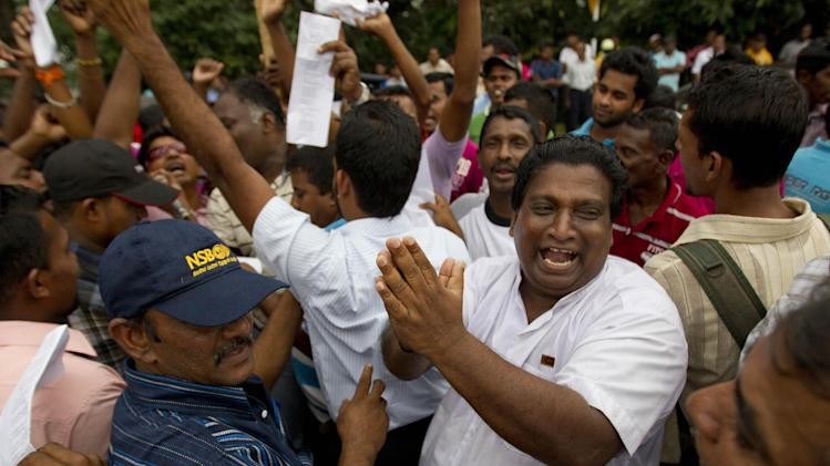 Supporters of Sri Lanka's president Mahinda Rajapaksa celebrate upon hearing the result of the vote to  impeach the country's Chief Justice Shirani Bandaranayake in Colombo, Sri Lanka, Friday, Jan 11, 2013. Sri Lanka's Parliament voted overwhelmingly on Friday to impeach the chief justice, deepening a standoff between the judiciary and the government, which is controlled by the country's most powerful family. (AP Photo/Gemunu Amarasinghe)