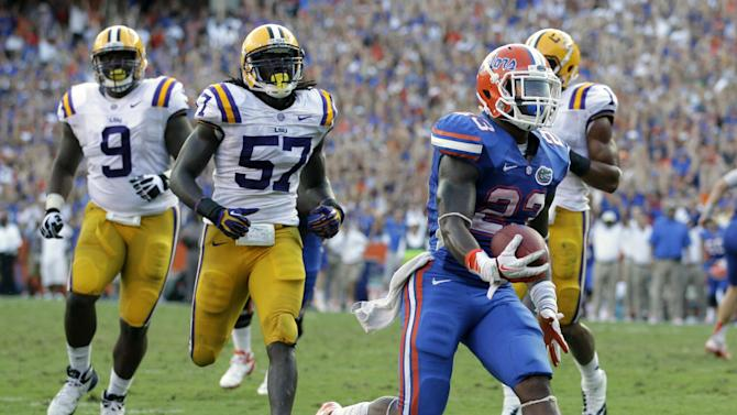 Florida running back Mike Gillislee, right, runs to the end zone on a 12-yard touchdown play past LSU defensive tackle Ego Ferguson (9) and linebacker Lamin Barrow (57) during the second half of an NCAA college football game, Saturday, Oct. 6, 2012, in Gainesville, Fla. (AP Photo/John Raoux)