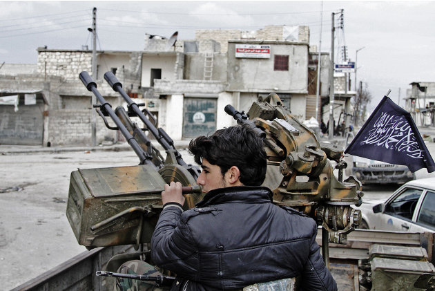In this Friday February 8, 2013, photo, a Free Syrian Army fighter sits behind an anti-aircraft weapon in Aleppo, Syria. Syrian rebels brought their fight within a mile of the heart of Damascus on Fri