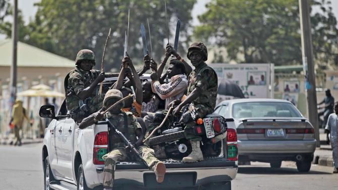 Soldiers and people carrying machetes ride on the back of a vehicle along a street in Gombe