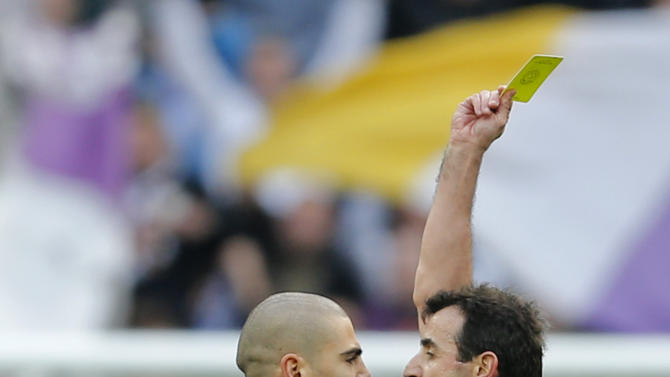 Barcelona's goalkeeper Victor Valdes, left is shown a yellow card after the final whistle during a Spanish La Liga soccer match against Real Madrid at the Santiago Bernabeu stadium in Madrid, Saturday March 2, 2013. Valdes continued to argue with the referee and was shown a red card seconds later. Real Madrid won the game 2-1. (AP Photo/Paul White)