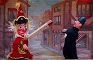 Mr Punch (L) hits a police puppet in a traditional Punch & Judy show during a weekend of performances and shows. Dozens of puppeteers gathered in central London on Sunday to celebrate 350 years of the Punch and Judy show, an anarchic English seaside entertainment known for its slapstick and casual violence