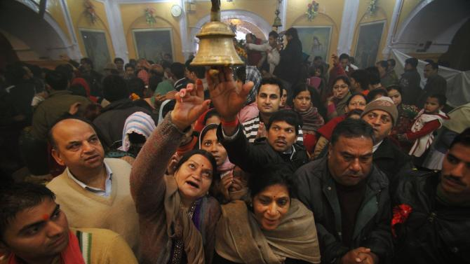Indian Hindu devotees try to ring a bell tied to a chain as they perform rituals at a temple during Mahashivratri festival celebrations in Jammu, India, Monday, Feb. 20, 2012. Hindus across the world are celebrating Mahashivratri, or Shiva's night festival. (AP Photo/Channi Anand)