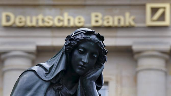 File photo of a statue is seen next to the logo of Germany's Deutsche Bank in Frankfurt