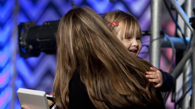 """Adonna Khare shares a hug with her daughter, Kinsey, 3, after winning the $200,000 ArtPrize Award for """"Elephants"""" at the fourth annual ArtPrize awards  Friday, Oct. 5 , 2012  in Grand Rapids, Mich. The annual art competition began Sept. 19. This year's installment features entries from 1,517 artists from 56 countries and 45 states. The works are on display at dozens venues across downtown Grand Rapids. A list of the 10 finalists for the public vote was earlier announced by organizers. (AP Photo/The Grand Rapids Press, Cory Morse) ALL LOCAL TV OUT; LOCAL TV INTERNET OUT"""