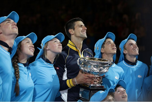 Serbia's Novak Djokovic poses with ball boys and ball girls after defeating Britain's Andy Murray in the men's final at the Australian Open tennis championship in Melbourne, Australia, Monday, Jan. 28