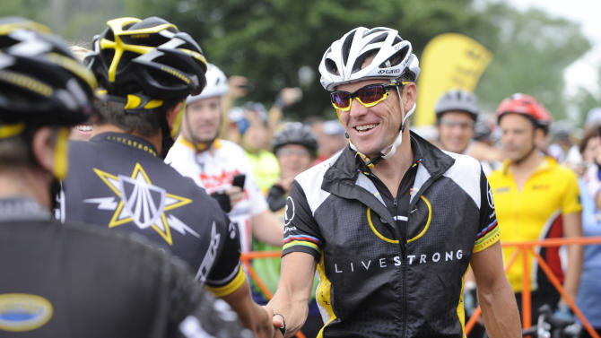 FILE - This Aug. 22, 2010 file photo shows Lance Armstrong, center, greeting fellow riders prior to the start of his Livestrong Challenge 10K ride for cancer in Blue Bell, Pa. Armstrong has cut formal ties with his cancer-fighting charity to avoid further damage brought by doping charges and being stripped of his seven Tour de France titles. (AP Photo/Bradley C. Bower, File)