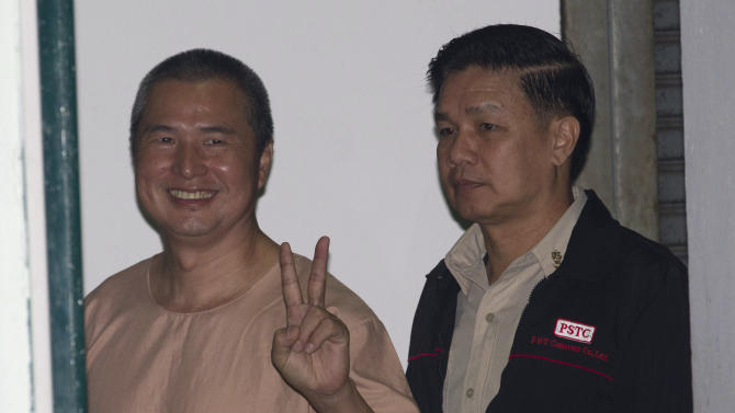 Activist Somyot Pruksakasemsuk, left, flashes v-sign before a court session at criminal court in Bangkok, Thailand  Wednesday, Jan. 23, 2013. The court has sentenced the prominent labor rights activist and magazine editor to 10 years in prison for publishing a pair of articles prosecutors said defamed the country's monarchy. (AP Photo/Sakchai Lalit)