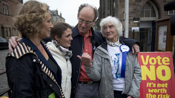 """Scottish independence referendum Yes supporter 83-year-old Edinburgh resident Isabelle Smith, right, who lived in the U.S. for three decades, poses for a photograph with her family members, from left, her niece Lynn Wilson, 52, of Zurich, her granddaughter Jean Thomae, 23, of Washington DC, and her son John Smith, 52, of Atlanta, after an interview with The Associated Press outside a polling place in Edinburgh, Scotland, Thursday, Sept. 18, 2014.  Polls have opened across Scotland in a referendum that will decide whether the country leaves its 307-year-old union with England and becomes an independent state.  Smith's three children and seven grandchildren are all American, and several flew to Scotland for the referendum _ """"to cocoon me in love,"""" she said.  (AP Photo/Matt Dunham)"""