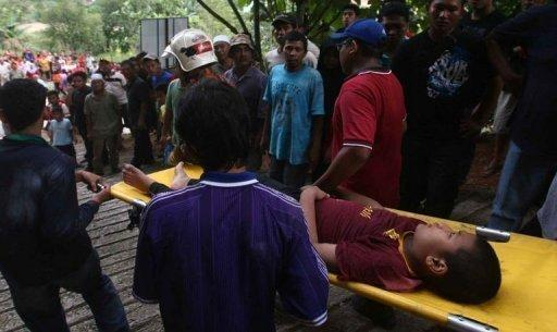 Emergency teams carry out an injured boy at the site of a landslide that hit an orphanage in Hulu Langat, Selangor. A close-knit village on the outskirts of the Malaysian capital was grieving for the deaths of 16 people, mostly children, after an orphanage was hit by a devastating landslide