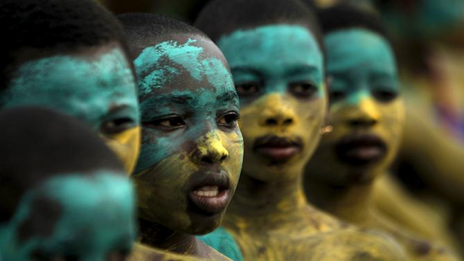 Youth with painted faces take part in a parade during the Popo (Mask) Carnival of Bonoua, in the east of Abidjan