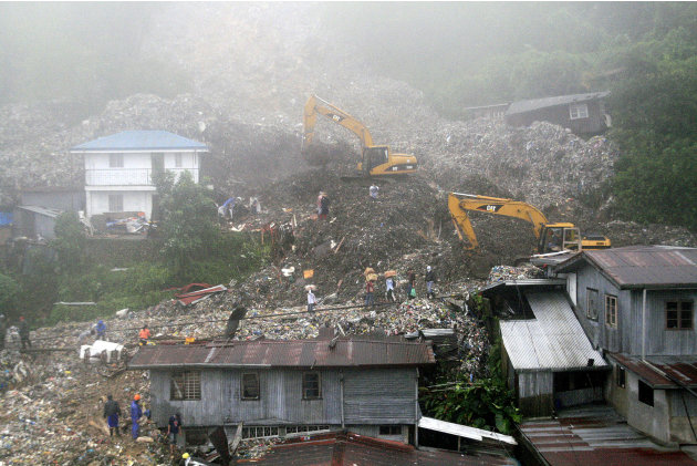Rescuers and volunteers try to clear piles of garbage under thick fog in Baguio City, northern Philippines on Monday Aug. 29, 2011. Several tons of garbage buried some shanties after a dumpsite's conc