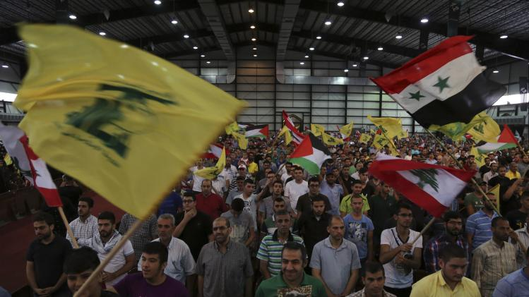 "Hezbollah supporters wave Lebanese, Syrian, Palestinian and Hezbollah flags as they listen to their leader Sayyed Hassan Nasrallah addressing his supporters during a rally to mark ""Quds (Jerusalem) Day"" in Beirut's southern suburbs"