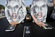 South Korean staff wear t-shirts showing the face of Lady Gaga at an information desk ahead of a concert outside Seoul's Olympic Stadium