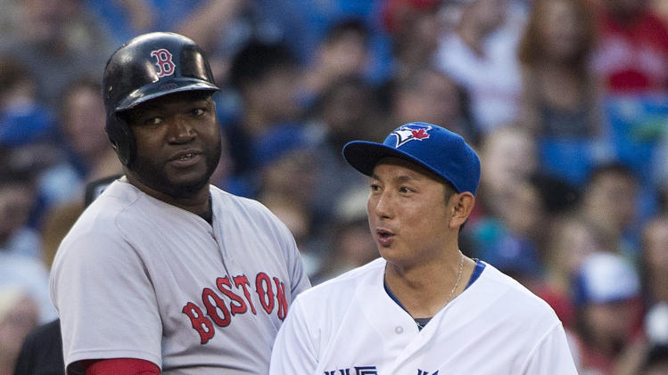 Toronto Blue Jays third baseman Munenori Kawasaki, right, receives a hug from Boston Red Sox David Ortiz, left, during the fourth inning of a baseball game, Tuesday, July 22, 2014 in Toronto. (AP Photo/The Canadian Press, Nathan Denette)