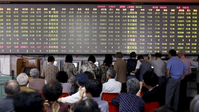 FIle photo investors looking at screens showing stock information at a brokerage house in Shanghai