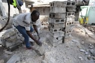 A Haitian collects usable bricks from a quake-destroyed home in Port-au-Prince after last year's deadly earthquake. Hundreds of thousands of Haitians living in squalid makeshift camps hunkered down Wednesday as lashing rain and wind from the outer bands of Tropical Storm Emily hit the quake-stricken country