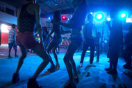 In this Dec. 8, 2012 photo, people dance during a funk &quot;baile,&quot; or party, in a slum in western Rio de Janeiro, Brazil. A 2007 law that had made it virtually impossible to hold the traditional open-air funk parties in favelas was repealed in 2009, and the musical genre was recognized as a cultural movement. Dance face-offs between performers of passinho, a type of break dancing associated with Rio&#39;s funk scene, now come with corporate sponsorship. (AP Photo/Felipe Dana)