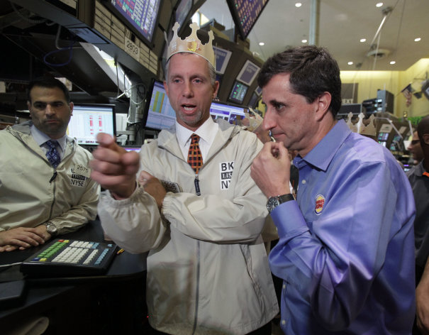 Burger King Corp. CEO Bernardo Hees, right, talks with specialist Donald Himpele, center, after his company's shares began trading on on the floor of the New York Stock Exchange Wednesday, June 20, 2012. Burger King's return to the Big Board wasn't through an initial public offering. 3G Capital announced an unusual deal in April to sell a minority stake to Justice Holdings Ltd., a London-based entity that was specifically set up to invest in another company. (AP Photo/Richard Drew)