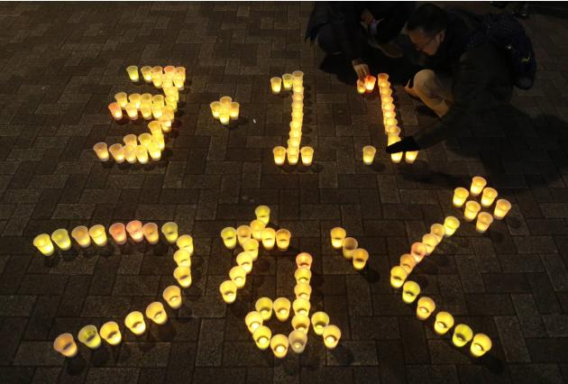 People arrange electric candles to form a message during a candle light demonstration to pay tribute to the victims of the March 11, 2011 earthquake and tsunami that killed thousands and to protest ag