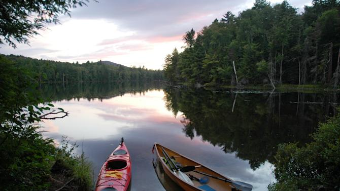 "In this Aug. 20, 2012 photo, a kayak and solo canoe rest at a campsite on East Pine Pond in the Saranac Lakes Wild Forest at Saranac Lake, N.Y.  A new guidebook, ""Adirondack Paddling: 60 Great Flatwater Adventures,"" is due out this year, aimed at the growing number of people exploring the expanding opportunities for paddlers in the Adirondack Park. (AP Photo/Mary Esch)"