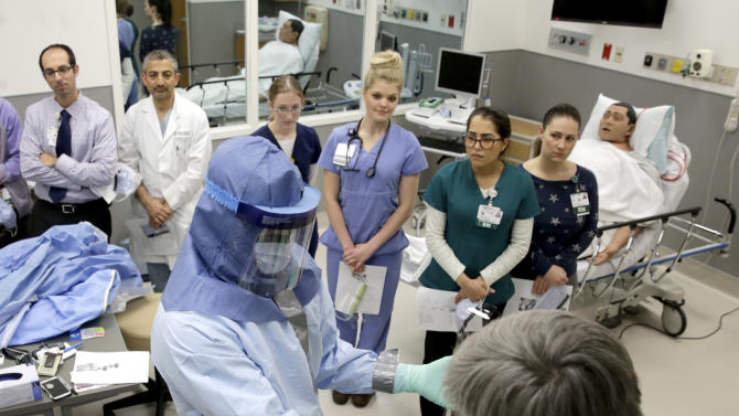 FILE - In this Oct. 16, 2014, file photo, registered nurse Keene Roadman, stands fully dressed in personal protective equipment, as he and registered nurse Fred Serafin, right, demonstrate proper protective procedures to doctors and nurses during a training class at the Rush University Medical Center in Chicago. The Centers for Disease Control and Prevention released new guidelines Monday, Oct. 20, for how health workers should gear up to treat Ebola patients. (AP Photo/Charles Rex Arbogast, File)