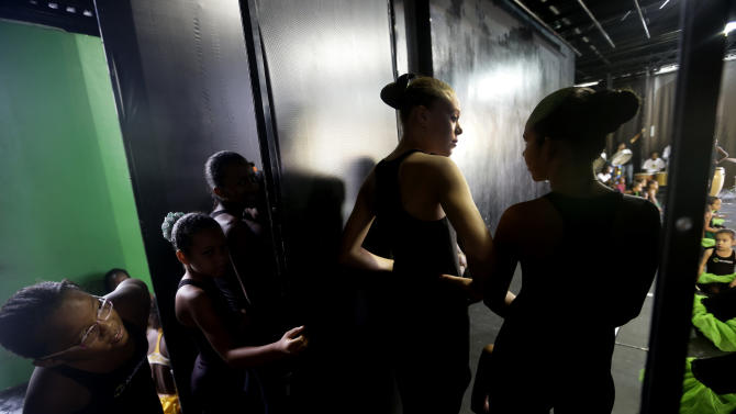 Dancers from the Afro Reggae cultural center peer from backstage before performing before members of London's Royal Opera House in the Vigario Geral slum in Rio de Janeiro, Brazil, Saturday, March 2, 2013. This past week Royal Ballet dancers shared their knowledge and advice with promising artists during an education symposium between the company and the cultural arts center Afro Reggae. (AP Photo/Silvia Izquierdo)