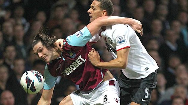 Manchester United's Rio Ferdinand (right) and West Ham United's Andy Carroll (left) battle for the ball