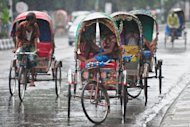 Bangladeshi rickshaw drivers take shelter from the rain in Dhaka during heavy storms in July. At least 19 people were killed and an estimated 1,500 fishermen are missing after more tropical storms smashed into Bangladesh's southern coastal islands and districts