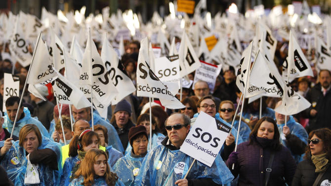 """People march as they carry banners reading, """"SOS, disability"""" during a protest against government austerity measures affecting disabled people by reducing services, closing disability centers and forcing care workers from their jobs in Madrid, Spain, Sunday, Dec. 2, 2012. More than 10,000 people, many in wheelchairs or being led by guide dogs, marched in a demonstration with the slogan """"SOS Disability: Save our Rights, Inclusion and Welfare."""" Health care spending falls under the responsibility of regional governments, many of which are indebted. Some local administrations have failed to pay medical centers, forcing cuts in services and a slow-down in the distribution of medicine. (AP Photo/Andres Kudacki)"""