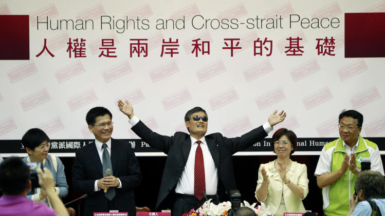 Chinese activist Chen Guangcheng, center, gestures as he speaks to lawmakers and human rights supporters at the legislature in Taipei, Taiwan, Tuesday, June 25, 2013. (AP Photo/Wally Santana)