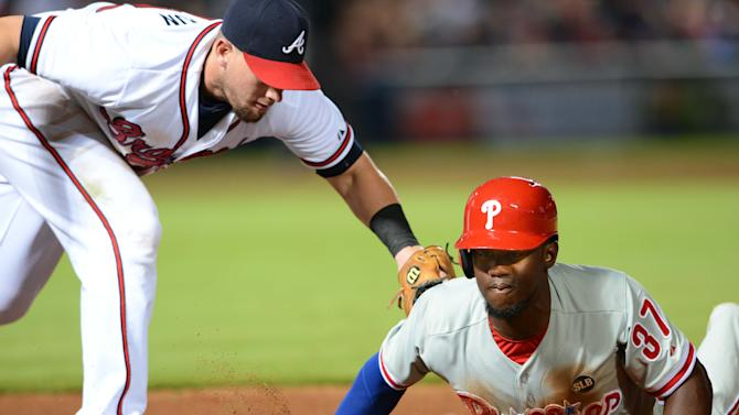 Philadelphia Phillies center fielder Odubel Herrera is safe diving back to first base on a pick-off attempt as Atlanta Braves first baseman Chris Johnson applies the tag during the seventh inning of a baseball game Friday, July 3, 2015, in Atlanta. (AP Photo/Jon Barash)