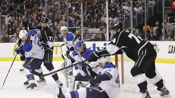 Los Angeles Kings' Dwight King, right, reaches for the puck against St. Louis Blues' Roman Polak, bottom, of Czech Republic, during the second period in Game 3 of a first-round NHL hockey Stanley Cup playoff series in Los Angeles, Saturday, May 4, 2013. (AP Photo/Jae C. Hong)