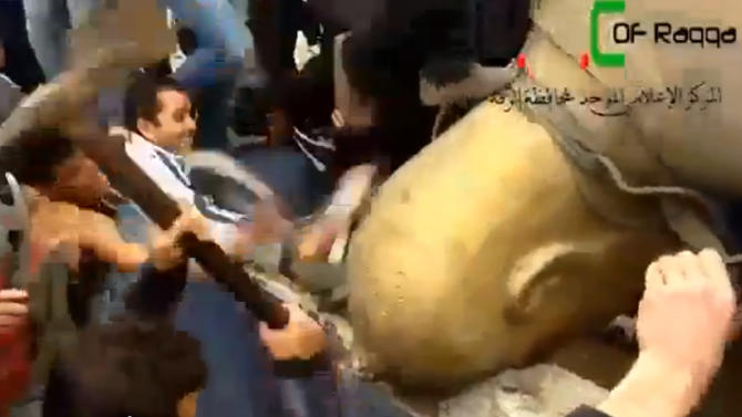 In this Monday, March 4, 2013 image taken from video obtained from Ugarit News, which has been authenticated based on its contents and other AP reporting, Syrians attack a fallen statue of former Syrian President Hafez Assad in a central square in Raqqa, Syria. Syrian rebels pushed government troops from most of the northern city of Raqqa Monday, setting off celebrations in a central square where scores of cheering protesters tore down a bronze statue of President Bashar Assad's late father and predecessor, activists said. (AP Photo/Ugarit News via AP video)