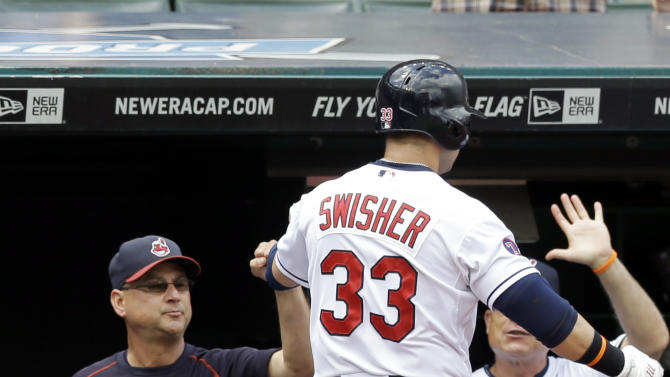 Cleveland Indians' Nick Swisher is congratulated by manager Terry Francona, left, after hitting a solo home run off Texas Rangers starting pitcher Colby Lewis in the second inning of a baseball game, Wednesday, May 27, 2015, in Cleveland. (AP Photo/Tony Dejak)